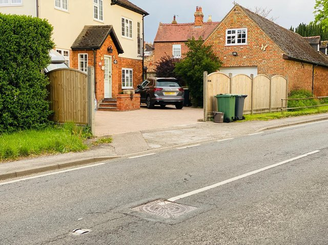 Lesley's driveway and an Anglian Water manhole cover.